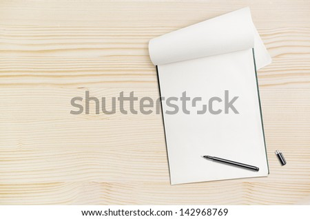 Blank notepad with pen on wood table, free space for text - stock photo