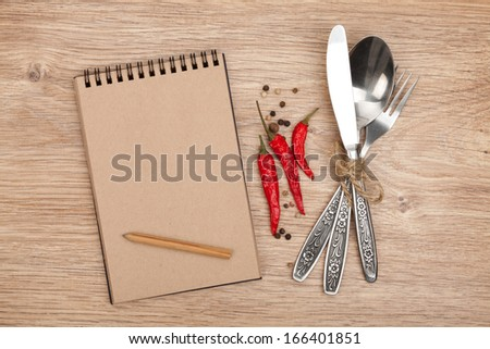 Blank notepad with pencil and silverware set on wooden table - stock photo
