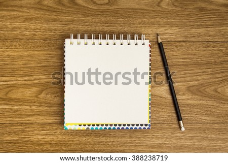 Blank notepad with pencil on wood table.
