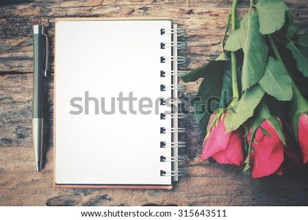 Blank notepad with red rose and pen