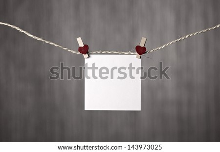 blank of paper with clothespeg with heart, clipping on clothesline, on grey blurred background
