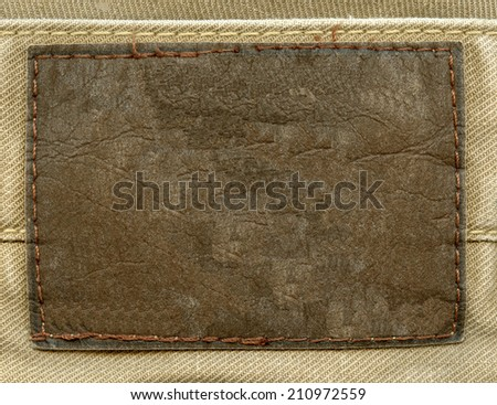 blank old  brown leather label on fabric background