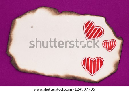 blank old burnt paper and hearts on purple background