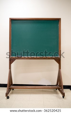 Blank old chalkboard in college classroom - stock photo