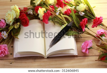 Blank old notebook, feather and flower arranged on wood table as vintage still life