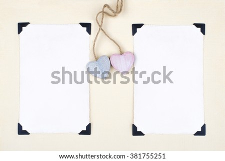Blank old photos for your pictures, with photo corners on aged paper with two wooden hearts. - stock photo