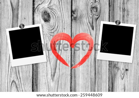Blank old photos on clips and red heart on color wooden background - stock photo