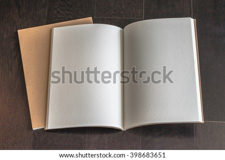 Blank open book, catalog, magazines, brochure, note template w/ paper texture on dark brown color wood table/ wooden floor background: Empty textured note book pages on timber backdrop for adding text - stock photo