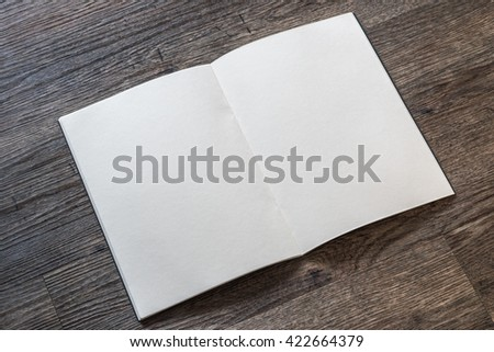Blank open book, catalog, magazines, brochure, note template w/ paper texture on dark grey color wood table/ wooden floor background: Empty textured note book pages on timber backdrop for adding text - stock photo