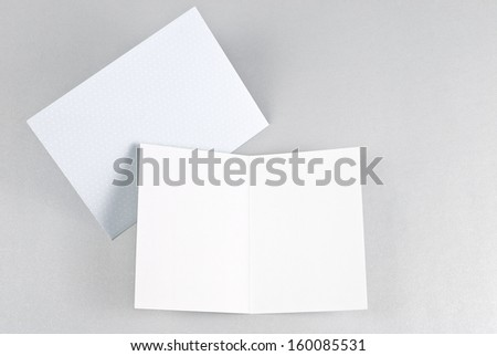 Blank open card and blue envelope over grey background - stock photo