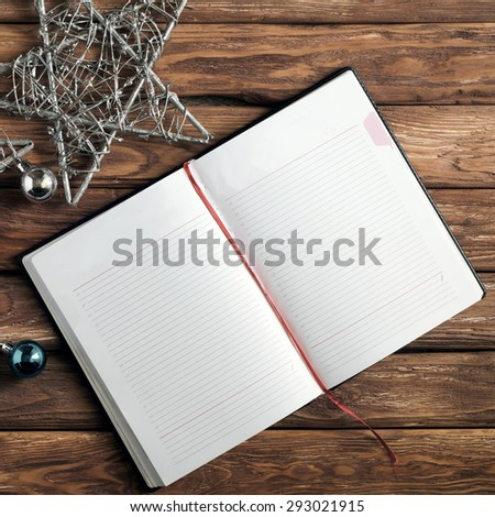 Blank open notebook for records on the old wooden table. Near the notepad lies  New Year Three stars and toys