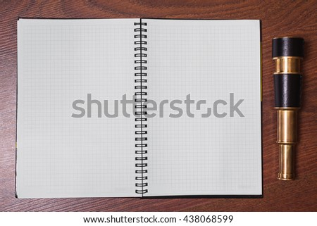 blank open notebook on a wooden background, telescope, space for text
