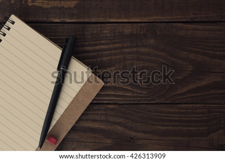 Blank open notebook with lined papers with pen on wooden table. Retro style. Top view with copy space. - stock photo
