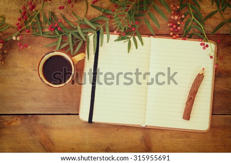 blank open vintage notebook, old paper and wooden pencil next to cup of coffee over wooden table. ready for mockup  - stock photo