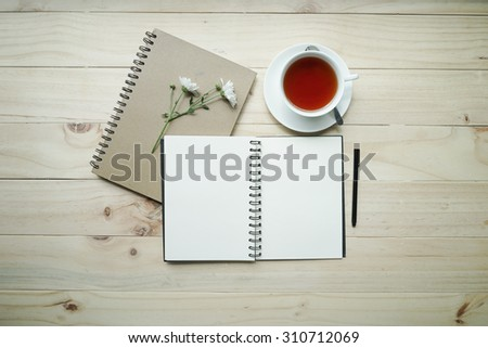 blank opened notebook with cup of tea and flowers on wooden table. Top view. Writing concept