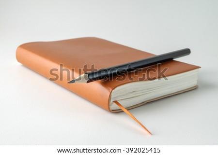 blank orange leather diary and pencil on white desk - stock photo