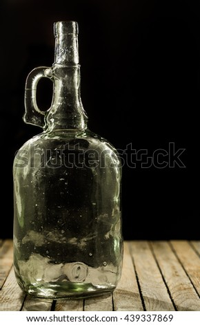 blank, original, glass bottle on a black and wooden background