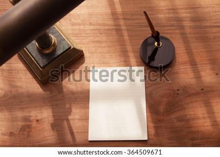 Blank pad of paper on a old desk with an old brass lamp and pen stand. - stock photo