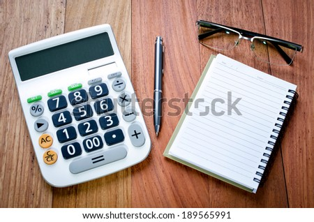 Blank Page notebook and calculator on the wooden desk background