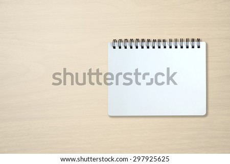 Blank page of notebook on beige office wooden table. use for background in business concept.