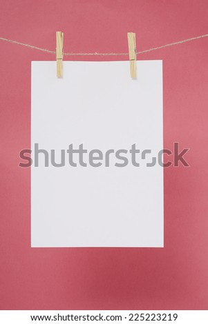 Blank page on washing line against pink background