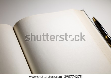 Blank pages in an open book with a pen - stock photo