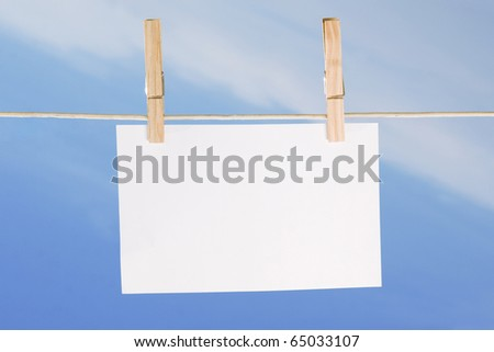 blank paper and clothes peg on blue sky background - stock photo
