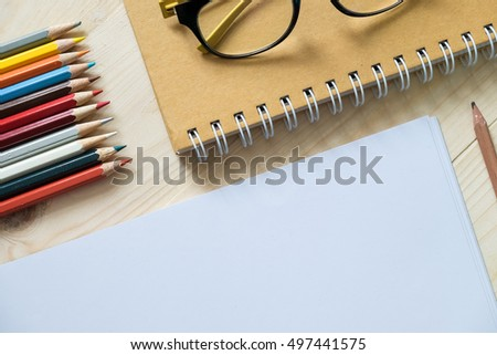 blank paper and colorful pencils and glasses on old wooden table with mornning light.