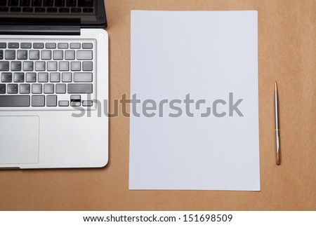 blank paper and laptop on table - stock photo