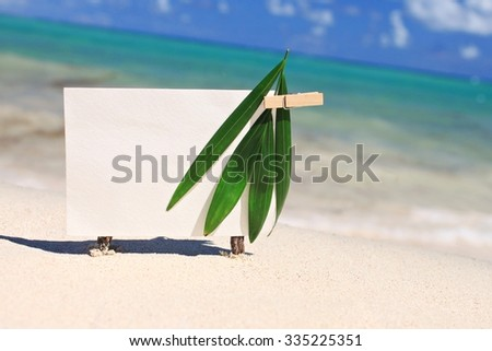 Blank paper card for writing text on sand, decorated with palm leaves, caribbean sea shore. Warm toned. - stock photo