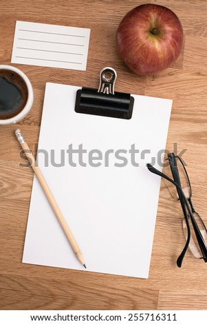 Blank paper, coffee, glasses and apple on the office table - stock photo