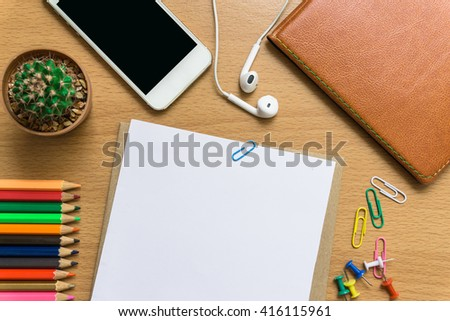 blank paper,  color pencil, and smart phone on wood desk / can you write text message / copy space / top view - stock photo