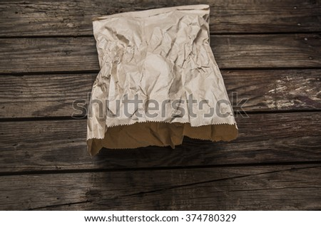 Blank paper craft shopping bag on wooden table with copy space - stock photo