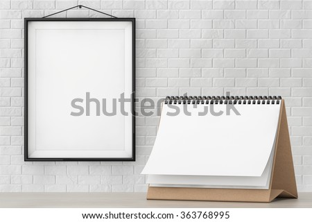 Blank Paper Desk Spiral Calendar in front of Brick Wall with Blank Frame extreme closeup - stock photo