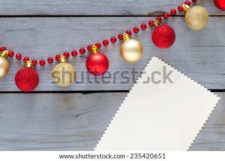Blank paper for christmas message with decoration on a wooden table. - stock photo