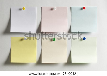 Blank paper, hanging on the wall with a colored pushpin - stock photo