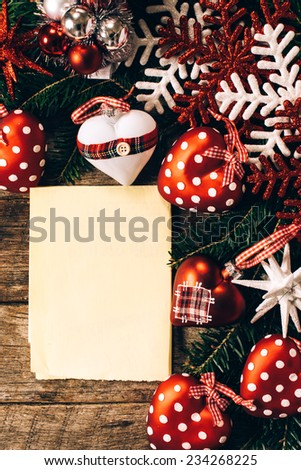 Blank paper in the middle of Christmas decorations on wooden background - stock photo