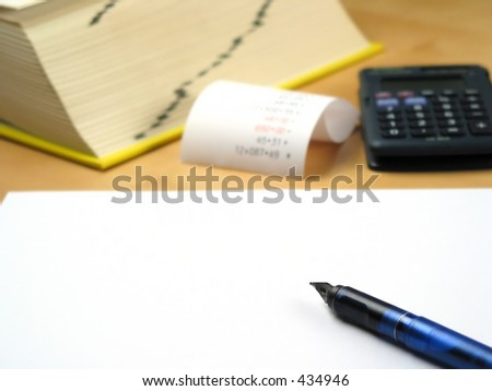 Blank paper infront of calculator, book and bills