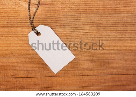 Blank paper label tag on wooden background - stock photo