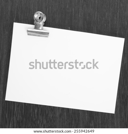 Blank paper note and metal clip on wood table