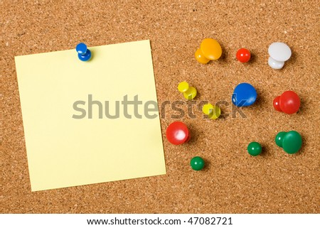 Blank paper note and office pins on cork board - stock photo