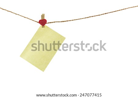Blank paper note hanging on rope by wooden clothespin heart shaped.