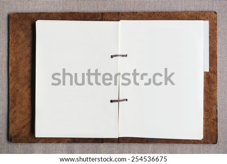 Blank paper page in leather cover folder - stock photo