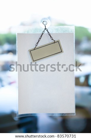 Blank paper sheet for message on glass office door - stock photo