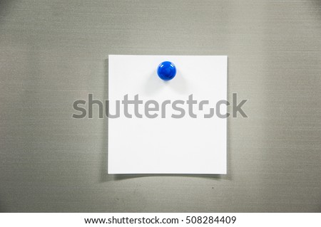 Blank paper sheet with blue magnet on refrigerator door