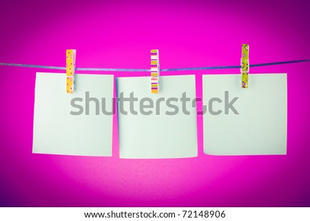 Blank paper sheets on a clothes line against the red background