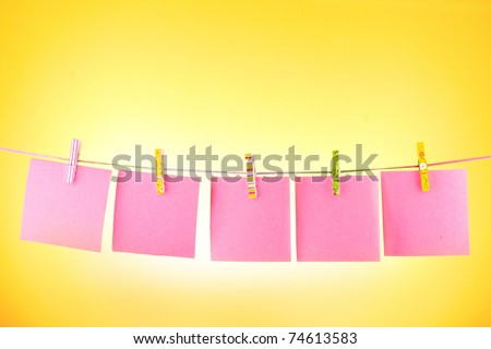 Blank paper sheets on a clothes line against the yellow background