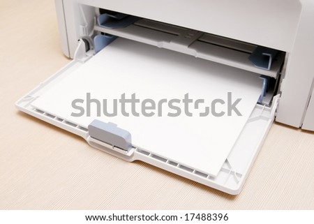 Blank paper-sheets ready for print in a printer. On the table in office. - stock photo
