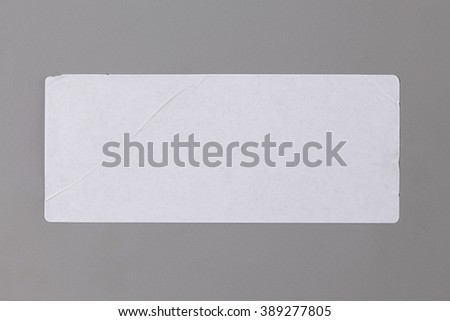 Blank Paper Tag. Label isolated on Grey Background. Sticker or Paper Adhesive with Wrinkles and Scratches. Close Up. Top View with Copy Space for Text or Image
