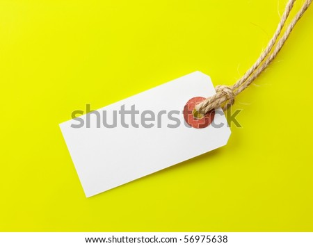 Blank paper tag with hemp string on yellow background. - stock photo